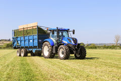拉扯在草地的现代蓝色拖拉机一辆拖车 库存图片