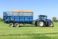 拉扯在草地的现代蓝色拖拉机一辆拖车 免版税库存照片