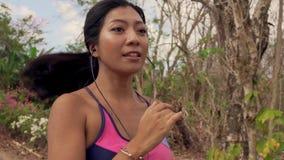拉扯在跑在足迹路跑步的年轻异乎寻常的适合和美丽的亚裔印度尼西亚妇女移动式摄影车样式射击的后面常平架  影视素材