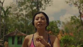 拉扯在跑在足迹路跑步的年轻异乎寻常的适合和美丽的亚裔印度尼西亚妇女移动式摄影车样式射击的后面常平架  股票视频