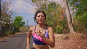 拉扯在跑在足迹路跑步的年轻异乎寻常的适合和美丽的亚裔印度尼西亚妇女移动式摄影车样式射击的后面常平架  股票录像