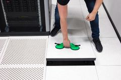 拉扯地垫的IT工程师使用吸杯在Datacenter 图库摄影