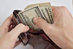 拉扯堆美国钞票USD货币,从一个皮革钱包的美元的男性手 图库摄影