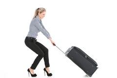 拉扯大行李的美丽的女孩 免版税图库摄影