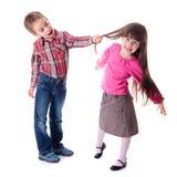 拉扯女孩的头发的男孩 免版税库存照片