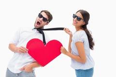 拉扯她的男朋友的浅黑肤色的男人由拿着心脏的领带 免版税库存照片