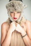 拉扯她的裘皮帽的年轻美丽的妇女  免版税图库摄影