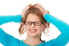 拉扯她的头发的沮丧的少年妇女 库存图片
