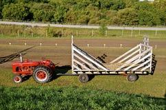 拉扯干草机架的拖拉机 库存照片