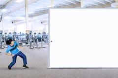 拉扯广告牌的蓬松卷发人在健身房 免版税图库摄影