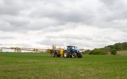 拉扯庄稼喷雾器的蓝色现代拖拉机 免版税库存照片