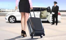拉扯手提箱的妇女留给机场白色大型高级轿车 库存图片