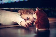 拉扯手的嬉戏的逗人喜爱的好奇孩子对玩具在葡萄酒样式的床下 库存照片