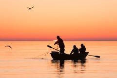拉扯捕鱼网的渔夫在日出的海 免版税库存照片