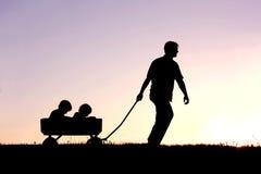 拉扯无盖货车的父亲剪影儿子在日落 免版税库存图片