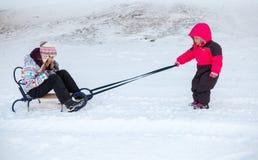 拉扯有姐妹的桃红色的小女婴一个雪撬 免版税库存照片