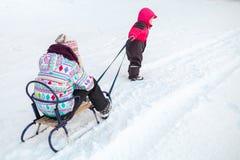 拉扯有姐妹的桃红色的小女婴一个雪撬 免版税图库摄影