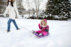 拉扯有孩子的愉快的母亲雪撬在冬天 库存照片