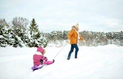 拉扯有孩子的愉快的父亲雪撬在冬天 库存照片
