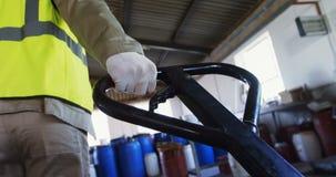 拉扯有条板箱的工作者一辆台车在橄榄色的工厂4k 影视素材
