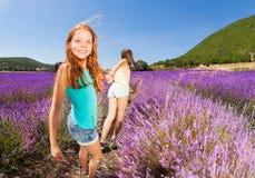 拉扯朋友的女孩握在淡紫色领域的手 免版税库存照片