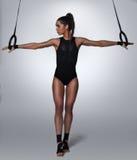拉扯杂技圆环的健身妇女 免版税库存照片