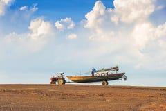 拉扯渔船的拖拉机 库存照片