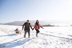 拉扯爬犁的父母女儿,运行 冬天na 免版税库存图片
