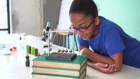 拉扯牛顿的摇篮球摇摆的非裔美国人的混杂的孩子在科学教室 股票录像
