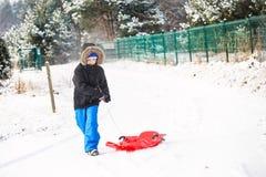 拉扯红色塑料雪撬的孩子 免版税库存照片