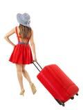 拉扯红色手提箱假期的妇女 夏天holida 免版税图库摄影