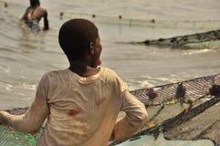 拉扯网的年轻渔夫 库存图片