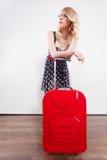 拉扯重的红色旅行袋子的妇女 免版税库存照片