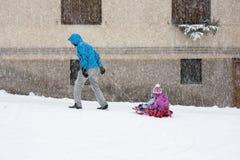 拉扯雪撬的爸爸孩子通过雪 库存照片