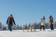 拉扯雪爬犁冬天乡下的年轻人 免版税图库摄影