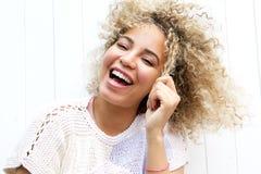 拉扯头发的微笑的少妇 库存照片