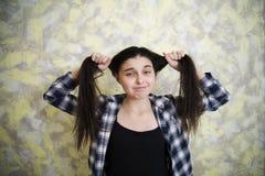 拉扯头发2的格子花呢上衣的青少年的女孩 库存照片