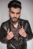 拉扯他的夹克的英俊的年轻时尚人 库存照片