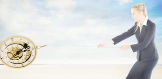 拉扯绳索的被聚焦的白肤金发的女实业家的综合图象 免版税库存照片