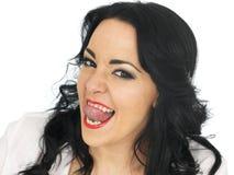 拉扯傻的面孔和伸出舌头的厚颜无耻的美丽的年轻西班牙妇女  免版税库存图片