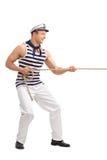拉扯绳索的年轻男性水手 免版税库存照片