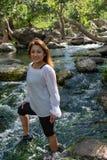 拉提纳妇女微笑的身分在与发光的头发的树荫下在与瀑布的一条小河在背景中 免版税图库摄影