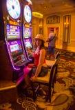 拉斯维加斯,美利坚合众国- 2016年5月06日:摆在老虎机的少妇在Excalibur旅馆里和 免版税库存照片