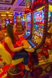 拉斯维加斯,美利坚合众国- 2016年5月06日:演奏老虎机的被集中的女孩在Excalibur旅馆里 免版税库存照片