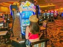 拉斯维加斯,美利坚合众国- 2016年5月05日:演奏老虎机的被集中的女孩在Excalibur旅馆里 库存照片