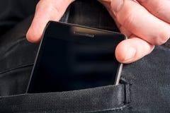 拉有拷贝空间的男性手一个黑智能手机从一个黑暗的裤子后面口袋里面 免版税库存照片