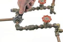 拉紧管道工程管组的水管工 图库摄影