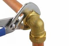 拉紧铜管道工程管组的水管工` s可调扳手 库存图片