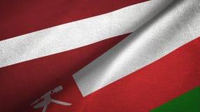 拉脱维亚和阿曼两旗子纺织品布料,织品纹理 库存例证
