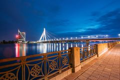 拉脱维亚里加 从道加瓦河的离开的堤防的看法对Vansu的缆绳停留了在明亮的夜照明的桥梁从 库存图片